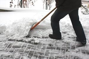 Mann beim Schneeschaufeln
